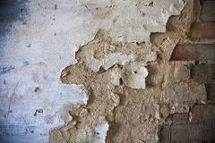 Damaged whitewashed plaster on the brick wall Royalty Free Stock Images