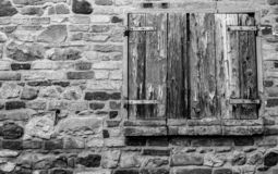 Window shutter of rural house, with brick wall and ancient stones stock image