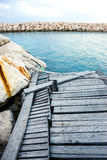 Damaged wooden pier with rock Royalty Free Stock Images