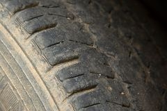 Damaged and worn black tire tread. Change time for safety royalty free stock photo