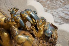 Damaged, worn gold statue of playful baby chinese dragon / lion. A sculpture of a baby chinese dragon / lion playing with the huge claw of its parent. Gold paint stock photos