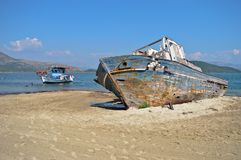 The life and death of a boat. A damaged and wrecked boat in the coast of a small Greek island and a living and still used boat in the background Royalty Free Stock Image