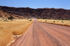 Damaraland road. Once, we were wandering on the damaraland roads. Suddenly, a car come, drawing something in our mind with its dust Royalty Free Stock Photo