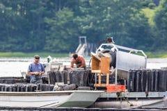 Damariscotta, Maine, U.S.A. - 2 luglio 2018: Ostrica che coltiva nel fiume di Damariscotta che controlla le trappole e le gabbie fotografia stock libera da diritti