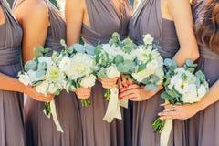 Damas de honor en marrón con el ramo de la boda Foto de archivo libre de regalías
