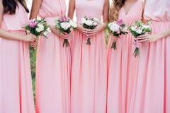 Damas de honor gloriosas en los vestidos rosados que sostienen las flores hermosas Fotografía de archivo