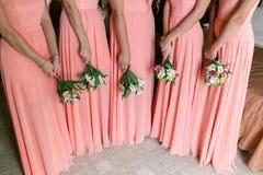 Damas de honra bonitas com os ramalhetes na casa Meninas modelo da beleza em vestidos de casamento coloridos Cinco povos Fotos de Stock Royalty Free