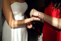 Damas de honra que ajudam obtendo o bracelete na mão da noiva em seu luxo imagem de stock