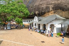 Dambulla golden temple cave complex buildinds is destination for. DAMBULLA, SRI LANKA -  NOV 2016: Golden temple cave complex buildinds carved in the rock is Stock Photo