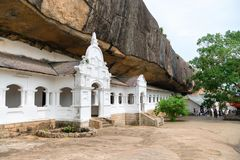 Dambulla golden temple cave complex buildinds is destination for. DAMBULLA, SRI LANKA -  NOV 2016: Golden temple cave complex buildinds carved in the rock is Royalty Free Stock Photo