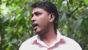 DAMBULLA, SRI LANKA - FEBRUARI 2014: Lokale gids die geneeskrachtig voordeel van verschillende kruiden in de het helen tuin verkl stock footage
