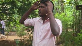 DAMBULLA, SRI LANKA - FEBRUARI 2014: Lokale gids die geneeskrachtig voordeel van verschillende kruiden in de het helen tuin verkl stock videobeelden