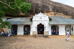 Dambulla golden temple cave complex buildinds is destination for. DAMBULLA, SRI LANKA -  NOV 2016: Golden temple cave complex buildinds carved in the rock is Royalty Free Stock Photography