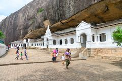 Dambulla golden temple cave complex buildinds is destination for. DAMBULLA, SRI LANKA -  NOV 2016: Golden temple cave complex buildinds carved in the rock is Stock Image