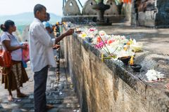 People place offerings with fragrant sticks, fresh flowers and b. DAMBULLA, SRI LANKA - NOV 2016: People place offerings with fragrant sticks, fresh flowers and stock images