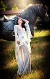 Dame à la mode avec la robe nuptiale blanche près du cheval brun Photos stock