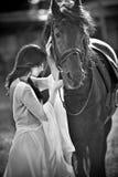 Dame à la mode avec la robe nuptiale blanche près du cheval brun Belle jeune femme dans une longue robe posant avec un cheval ami Image stock