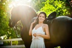 Dame à la mode avec la robe nuptiale blanche près du cheval brun en nature Belle jeune femme dans une longue robe posant avec un  Photographie stock libre de droits