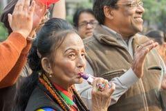 Dame âgée appréciant sa crème d'icre parmi les hommes Photo stock