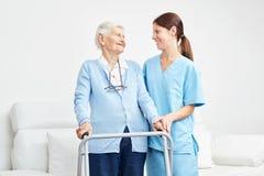Dame âgée apprend à marcher avec le marcheur dans la réadaptation photographie stock libre de droits
