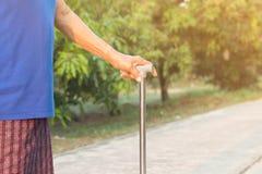 Dame âgée asiatique se tenant avec ses mains sur un bâton de marche, main Image stock