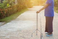 Dame âgée asiatique se tenant avec ses mains sur un bâton de marche, main Image libre de droits