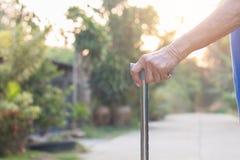 Dame âgée asiatique se tenant avec ses mains sur un bâton de marche, main Photos libres de droits