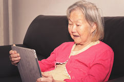 Dame âgée assise sur un sofa utilisant un comprimé d'écran tactile Image stock