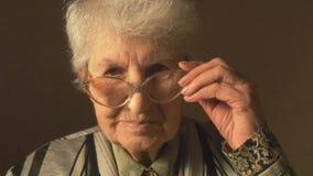 Dame âgée avec des lunettes regardant l'appareil-photo et le sourire banque de vidéos