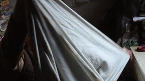 Dame âgée avec des sortes grises de cheveux par de vieilles choses, nettoie le lit dans sa vieille maison, seul vivant banque de vidéos