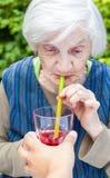 Dame âgée avec du jus potable de framboise de la maladie d'Alzheimer Image stock