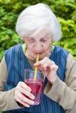 Dame âgée avec du jus potable de framboise de la maladie d'Alzheimer Photos libres de droits
