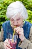 Dame âgée avec du jus potable de framboise de la maladie d'Alzheimer Photo libre de droits