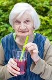 Dame âgée avec du jus potable de framboise de la maladie d'Alzheimer Photographie stock