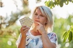 Dame âgée avec la médecine sur sa main Images stock