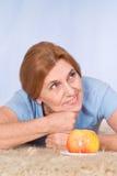 Dame âgée avec la pomme Images stock