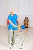 Dame âgée avec le marcheur tenant des pouces  Photographie stock