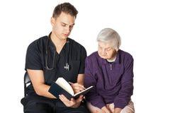Dame âgée avec le soignant lisant un roman Photo libre de droits