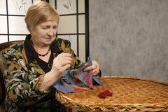 Dame âgée avec un pointeau et un amorçage Photographie stock