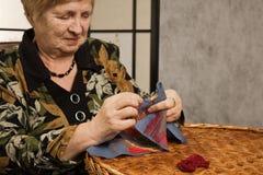 Dame âgée avec un pointeau et un amorçage Image stock