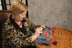Dame âgée avec un pointeau et un amorçage Photos stock