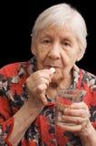Dame âgée boit une tablette image stock