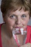 Dame âgée buvant l'eau minérale Photo stock