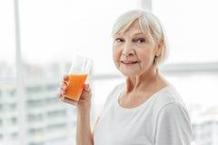 Dame âgée calme buvant la boisson fruitée Images stock