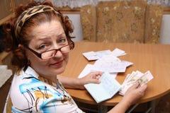 Dame âgée compte l'argent Photo libre de droits