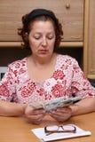 Dame âgée compte l'argent Photos libres de droits