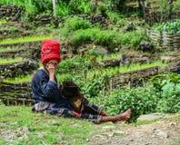 Dame âgée cousant sur la route rurale photos stock