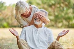 Dame âgée couvre ses yeux du ` s de mari Images stock