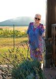 Dame âgée dans des lunettes de soleil se tenant avec une canne Image stock