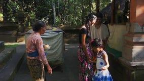 Dame âgée dans des vêtements locaux parle à de jeunes femelles le jour ensoleillé dans le village asiatique banque de vidéos